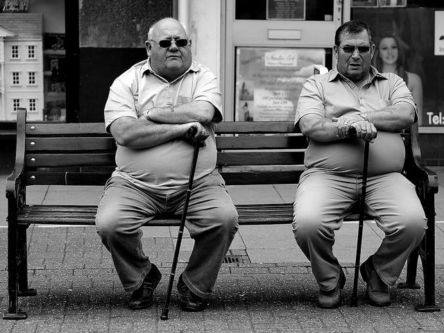 Mannen op bank met stok